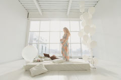 Young beautiful pregnant woman standing near window at home. Pregnancy, motherhood, people and expectation concept - close up of happy pregnant woman with big Stock Images