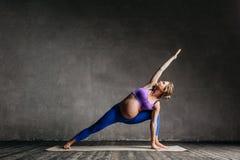 Young beautiful  pregnant yoga posing in studio Royalty Free Stock Photo