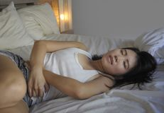 Young beautiful and pretty Asian Chinese woman lying on bed feeling ill and unwell suffering belly and stomach cramp and menstruat. Ion period pain holding her Stock Images