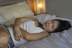 Young beautiful and pretty Asian Chinese woman lying on bed feeling ill and unwell suffering belly and stomach cramp and menstruat. Ion period pain holding her Stock Photo