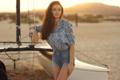 Young beautiful pretty girl sitting at sailing catamaran Stock Images