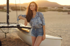 Young beautiful pretty girl sitting at sailing catamaran Stock Photos