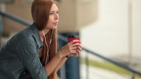 Young beautiful pretty girl sitting on the street with a cup of coffee. Young beautiful pretty girl walking along the street with a cup of coffee. The girl stock footage