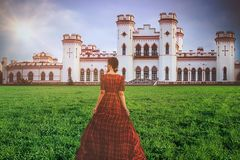 Young beautiful princess in a long red dress on the castle background in sunny day. Art processing.  stock photos