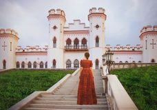 Young beautiful princess in a long red dress on the castle background in sunny day. Art processing.  royalty free stock photo
