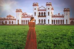 Young beautiful princess in a long red dress on the castle background in sunny day. Art processing.  royalty free stock image