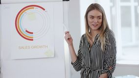 Young beautiful professional blonde business woman presenting sales diagram on flipchart at modern office meeting. Happy attractive female boss explaining stock video footage