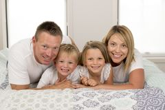 Young beautiful and radiant couple 30 to 40 years old smiling happy posing sweet lying on bed with little son and beautiful daught. Er at home bedroom in love royalty free stock photography