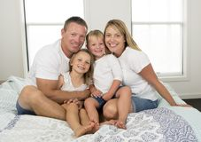 Young beautiful and radiant couple 30 to 40 years old smiling happy posing sweet lying on bed with little son and beautiful daught. Er at home bedroom in love stock image