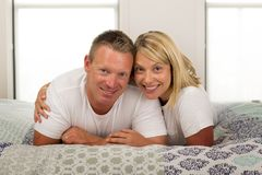 Young beautiful and radiant romantic couple 30 to 40 years old s. Miling happy in love posing sweet and cuddle lying on bed at home bedroom in successful husband royalty free stock image