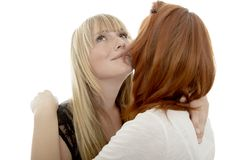 Young beautiful red and blond haired girls kiss Stock Images