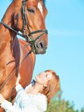 Young beautiful red  girl  with her horse in field Royalty Free Stock Photos