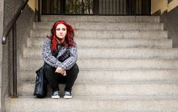 Young beautiful red hair girl sitting alone outdoors on the stairs of the building with hat and shirt feeling anxious and depresse stock images