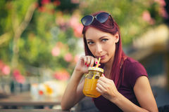 Young beautiful red hair woman drinking juice Stock Photo
