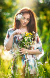 Young beautiful red hair woman holding a wild flowers bouquet in a sunny day. Portrait of attractive long hair female with flowers Stock Image