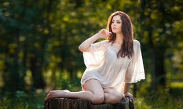 Young Beautiful Red Hair Woman Wearing A Transparent White Blouse Posing On A Stump In A Green Forest. Fashionable Sexy Girl