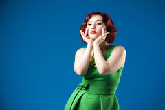 Young beautiful red-haired caucasian woman in green dress posing in studio on blue background, professional makeup and hairstyle Stock Photo