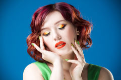 Young beautiful red-haired caucasian woman in green dress posing in studio on blue background, professional makeup and hairstyle Royalty Free Stock Photography