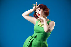 Young beautiful red-haired caucasian woman in green dress posing in studio on blue background, professional makeup and hairstyle Royalty Free Stock Images