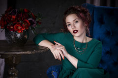 Young beautiful red-haired caucasian woman with professional makeup in green dress posing on blue sofa Stock Photography