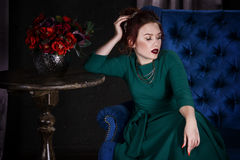 Young beautiful red-haired caucasian woman with professional makeup in green dress posing on blue sofa Stock Images
