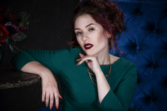 Young beautiful red-haired caucasian woman with professional makeup in green dress posing on blue sofa Stock Image