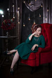 Young beautiful red-haired caucasian woman with professional makeup in green dress posing on red sofa Royalty Free Stock Images