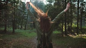 A young beautiful red-haired girl with a backpack is walking through a forest or park. Travel alone, hipster walker stock footage