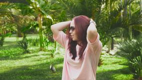 Young beautiful red-haired girl dancing in the park. woman in a mini skirt dancing in a tropical park on a background of