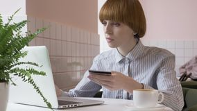 Young beautiful red-haired girl doing online shopping on the Internet, laptop, credit card, banking, application. 60 fps. 4k stock footage