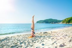 Young, beautiful, red-haired girl practices yoga on the beach. Stock Photo