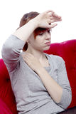 Young beautiful red haired girl on red sofa feels bad in front o Stock Image