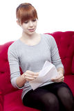 Young beautiful red haired girl sit on red sofa and received a l Stock Photos