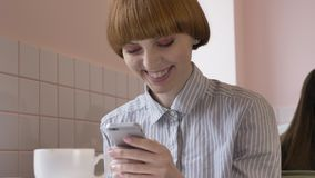 Young beautiful red-haired girl sitting in a cafe, using a smartphone, texting, smiling, laughing. 60 fps. 4k stock footage