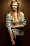 Young beautiful red-haired wearing trendy glasses. Portrait of a young beautiful red-haired wearing trendy glasses and casual clothes and posing over golden Stock Photo