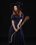 Young beautiful red-haired witch in the dark Stock Photos