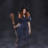 Young beautiful red-haired witch in the dark fog Stock Images