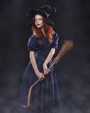 Young beautiful red-haired witch in the dark fog Stock Photo