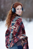 Young beautiful red-haired woman in blue headphones. And gloves. She is wrappening in a big scarf with ethnic pattern. She looks over her right shoulder. There Stock Photos