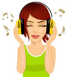 Young beautiful red haired woman enjoying the music with headphones Stock Photos