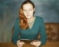 Young beautiful red-haired woman. Reading a book Stock Photo