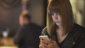 Young beautiful red-haired woman sitting in cafe or bar and using a smartphone. In Odessa stock video footage