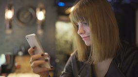 Young beautiful red-haired woman sitting in cafe or bar and using a smartphone. In Odessa stock footage