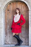 Young beautiful redhaired woman in front of the old door Stock Photos