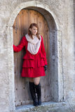 Young beautiful redhaired woman posing in front of the old door Stock Photography