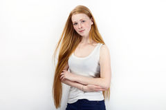Young beautiful redhead beginner model woman in white t-shirt blue jeans practicing posing showing emotions standing against white Royalty Free Stock Images