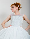 Young and beautiful redhead bride dressed wedding dress posing in studio Stock Photo