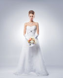 A young redhead woman in a white bridal dress Stock Images
