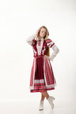 Young beautiful redhead folk dancer woman with gorgeous long hair in traditional authentic folk costume posing isolated on white. Young beautiful redhead folk royalty free stock image