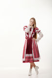 Young beautiful redhead folk dancer woman with gorgeous long hair in traditional authentic folk costume posing isolated on white. Young beautiful redhead folk royalty free stock images